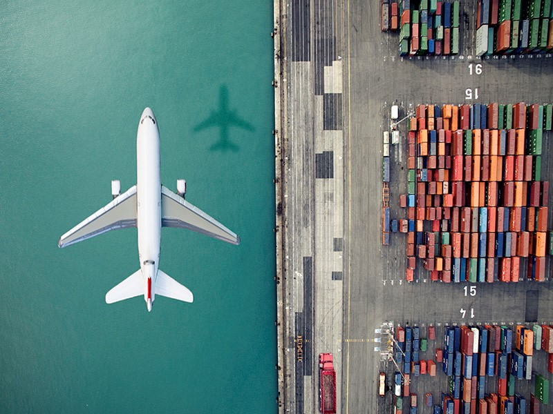 airplane flying over shipping containers