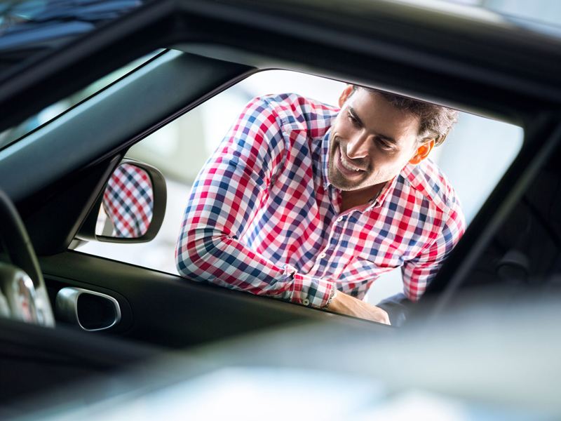man leaning in window of automobile