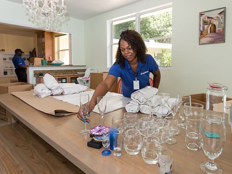 female mover packing glassware