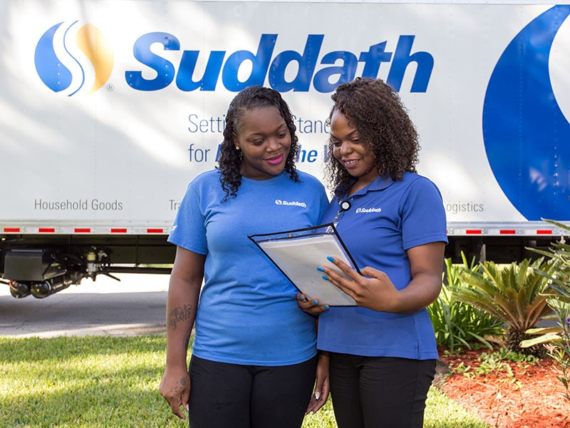 female moving team standing in front of suddath moving truck