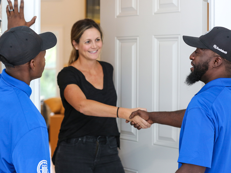jacksonville local movers shaking hands with woman at front door