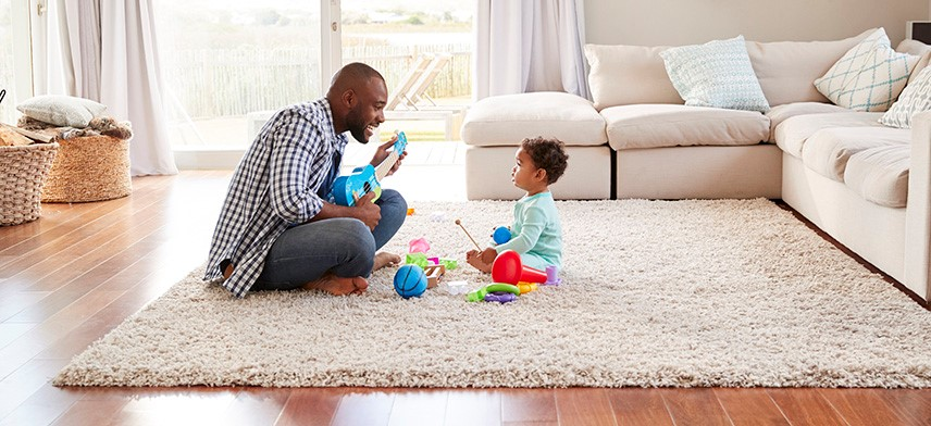 father and child playing on living room floor