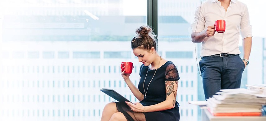 man and woman drinking coffee reviewing international corporate relocation