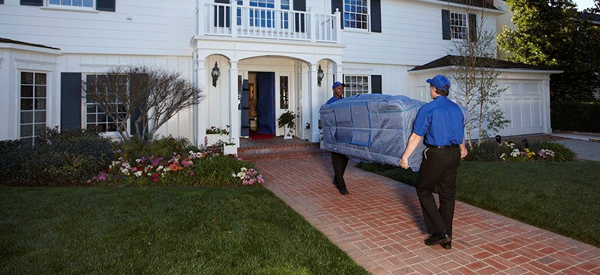 home movers carrying sofa into home