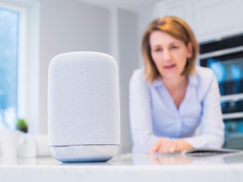 woman speaking to smart speaker in kitchen