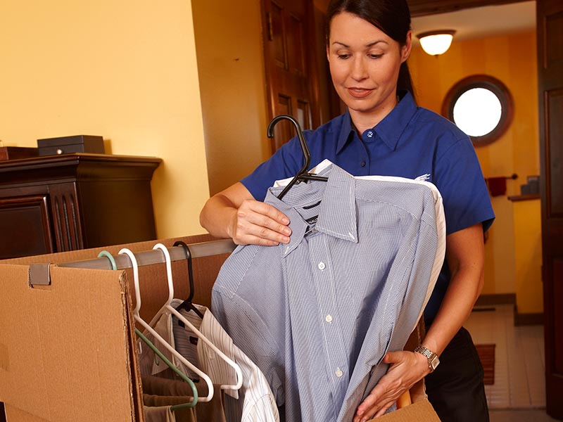 female mover packing clothing in wardrobe moving box