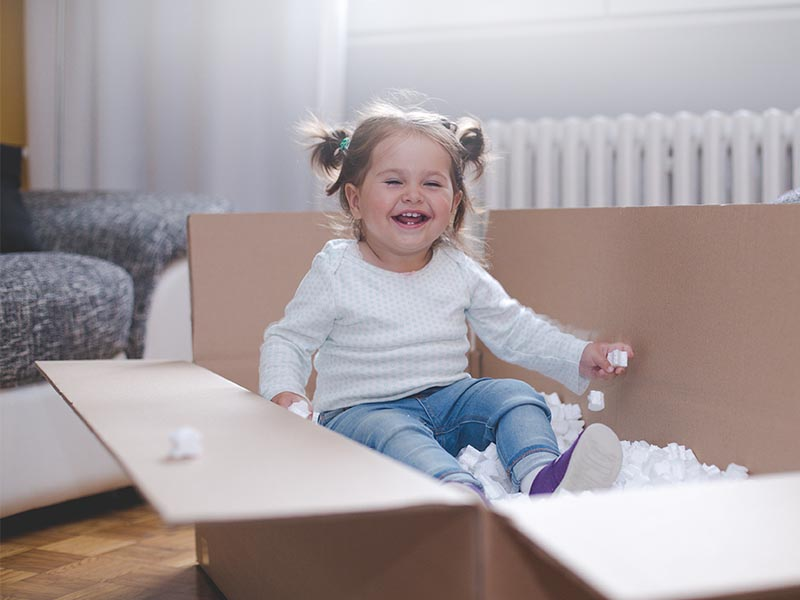 smiling toddler sitting in moving box with packing peanuts
