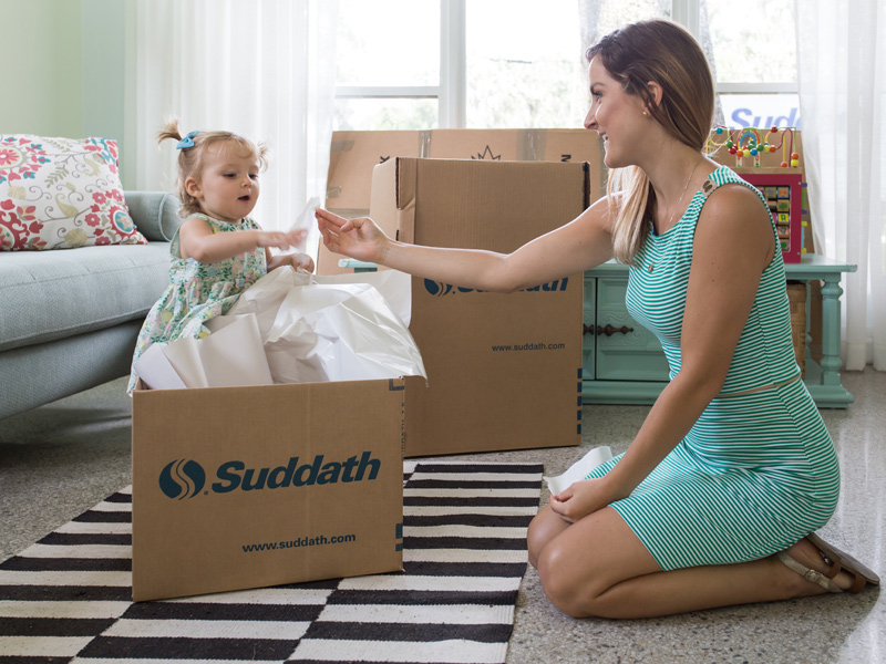 mother packing moving box for international move with female toddler