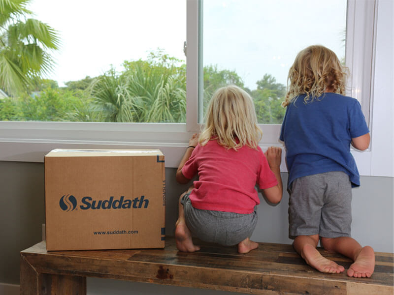 kids sitting on bench next to moving box looking out window