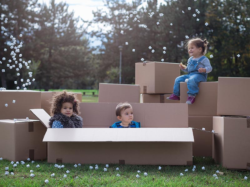 young kids playing in moving boxes outside