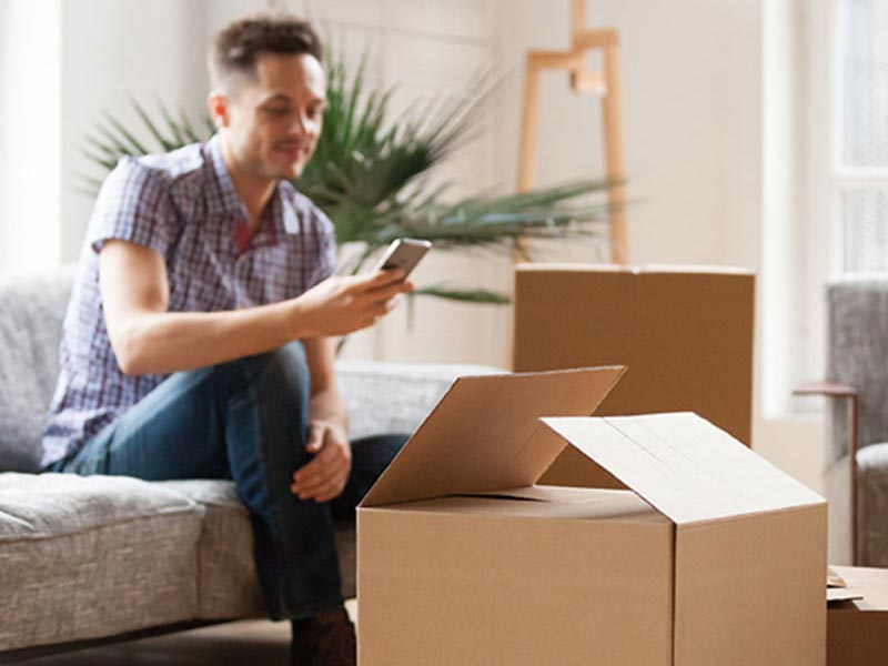 man sitting on sofa using mobile phone with open moving boxes