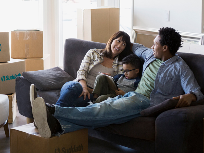 family sitting on sofa after home move