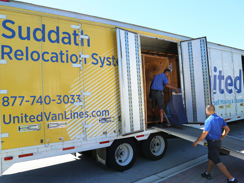 movers loading furniture on to moving truck