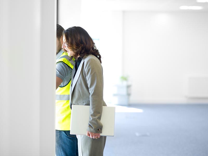man and woman doing space planning walkthrough of office space