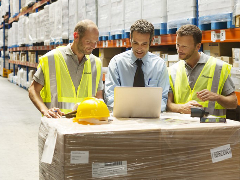 warehouse workers looking at laptop discussing supply chain logistics safety