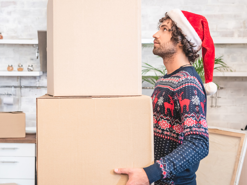 man holding moving boxes wearing festive hat