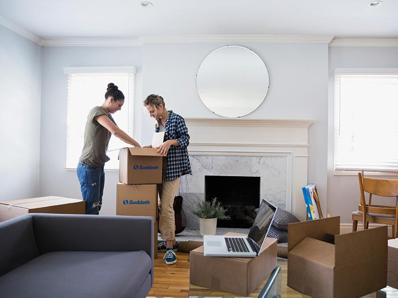 two women packing moving boxes for move
