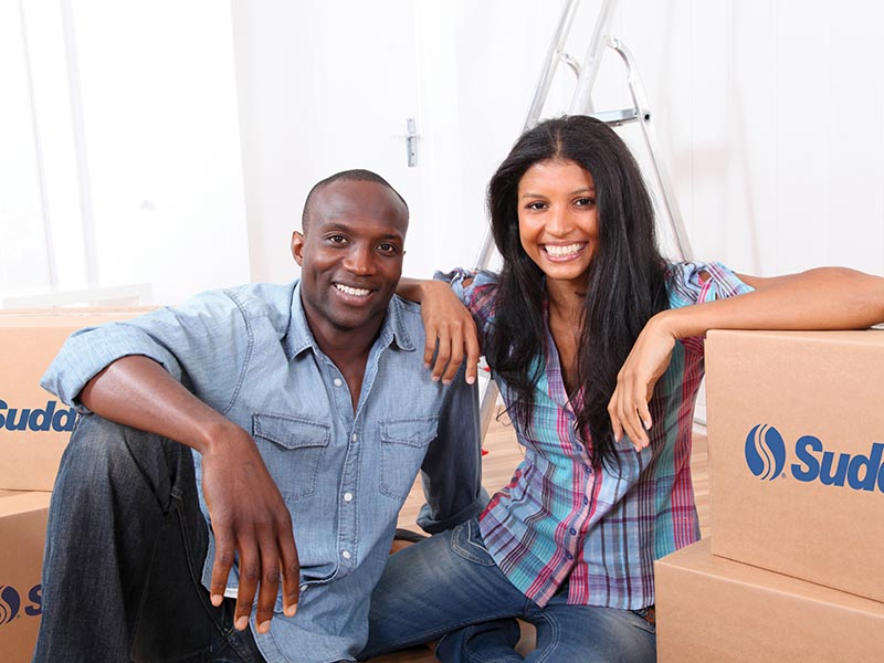 couple smiling surrounded by moving boxes