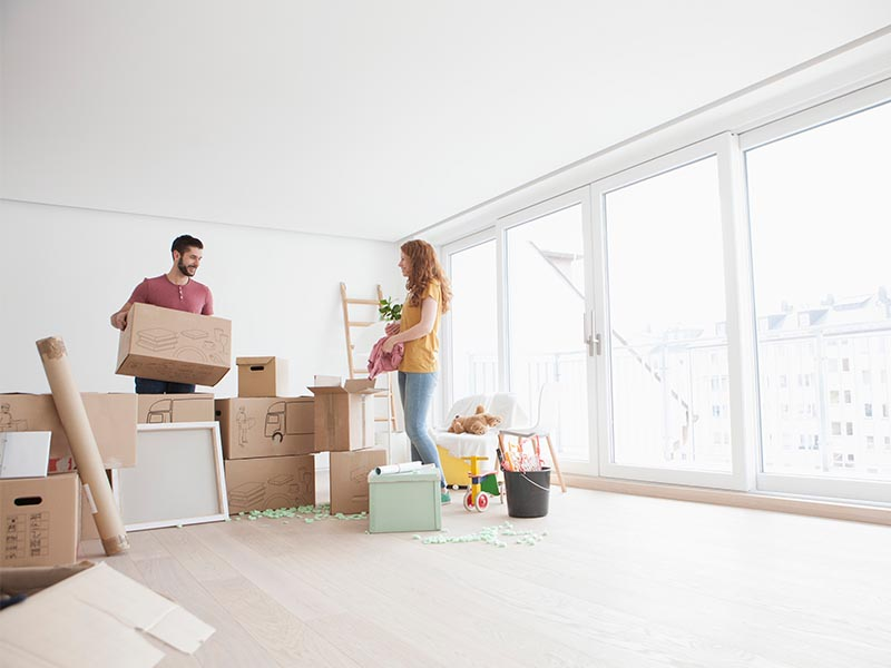 couple unpacking moving boxes in first home