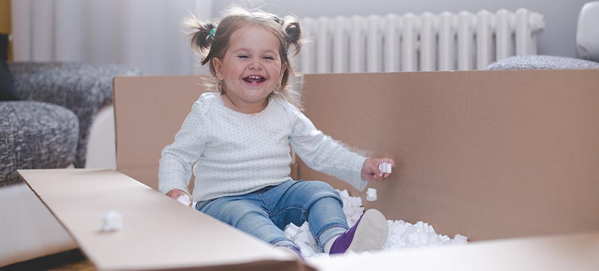 female toddler playing in moving box with packing peanuts