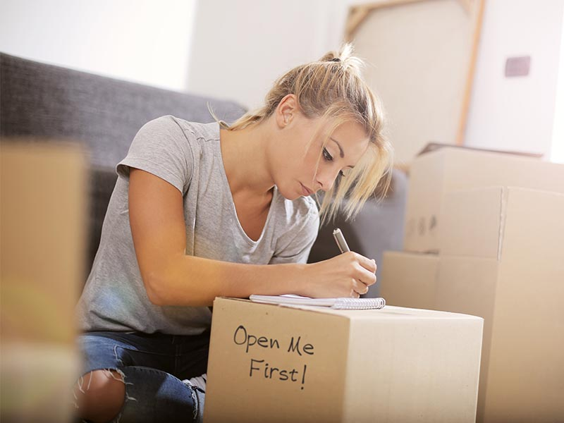 woman making move plans surrounded by moving boxes