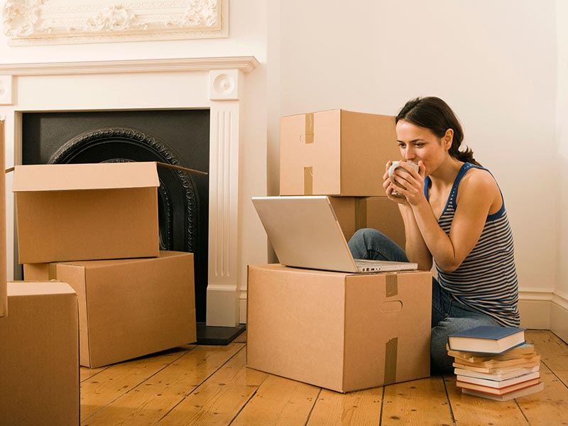 woman on laptop surrounded by moving boxes